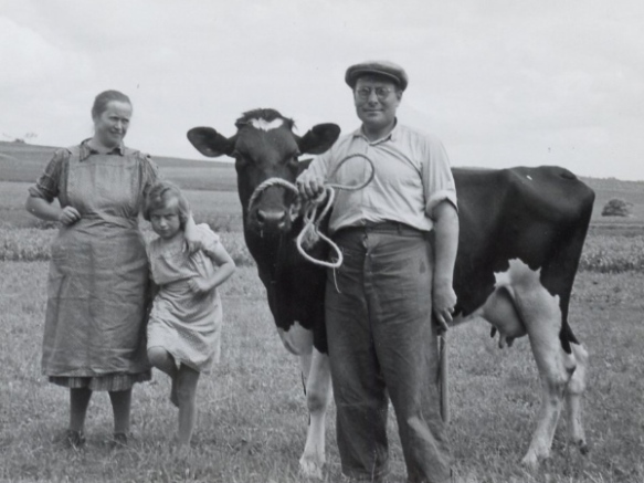 This German refugee family proudly poses with their heifer. Photo courtesy of Heifer International.