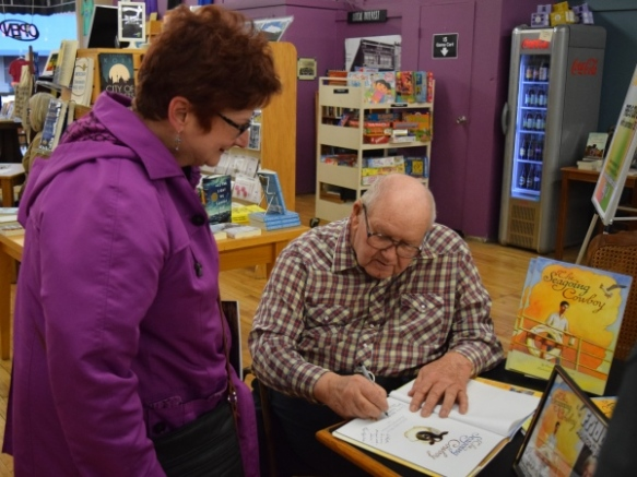 John Nunemaker adds his autograph to The Seagoing Cowboy at Better World Books, April 1, 2016.